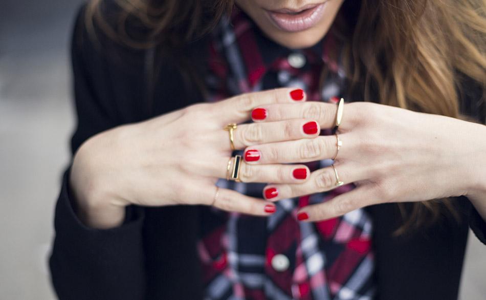 manicura roja y anillos look de street style con camisa de cuadros, pantalones pitillos de cuero, sneakers rojas de hakei y blazer