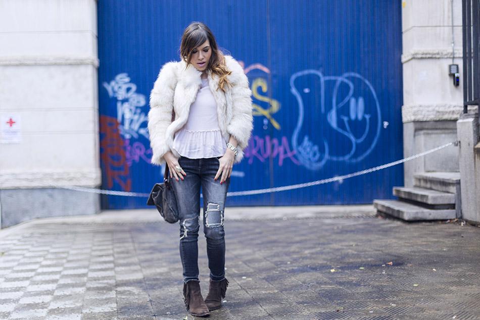 bárbara crespo en look de street style con chaqueta de falso pelo, top con volante en el bajo de hakei, jeans pitillo o skinny de mango y botines de flecos de sendra