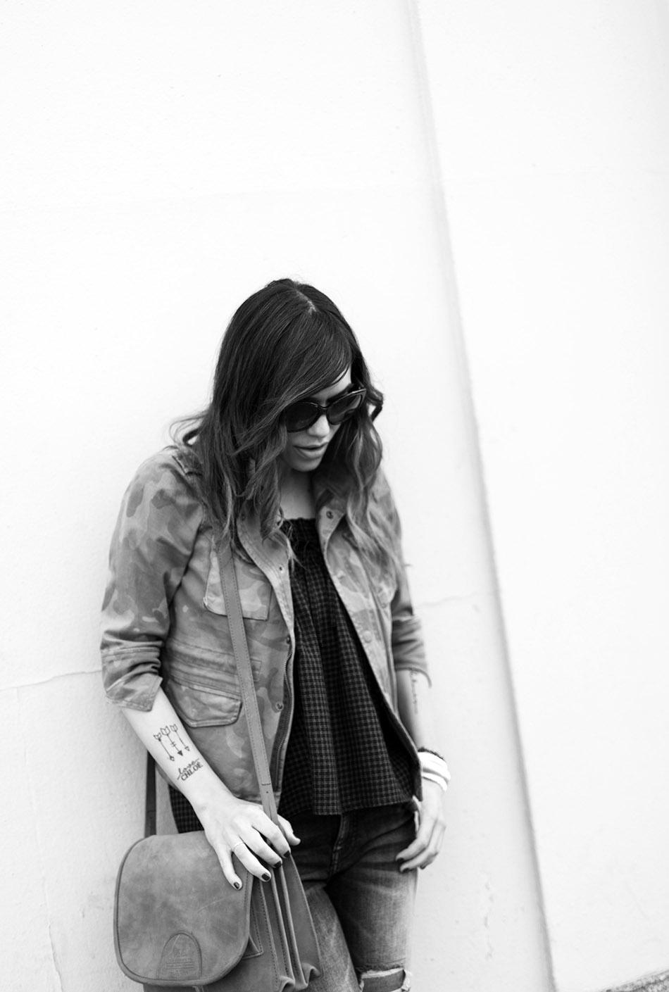 look de street style con chaqueta de estampado militar, top de cuadros vichy, pitillos y botines de flecos. bárbara crespo. foto en blanco y negro