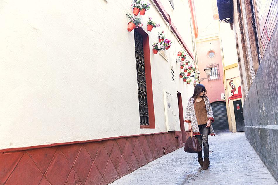 look de street style con chaqueta étnica, top de ante, jeans desgastados o ripped jeans, bolso andy de carolina herrera y botines de flecos
