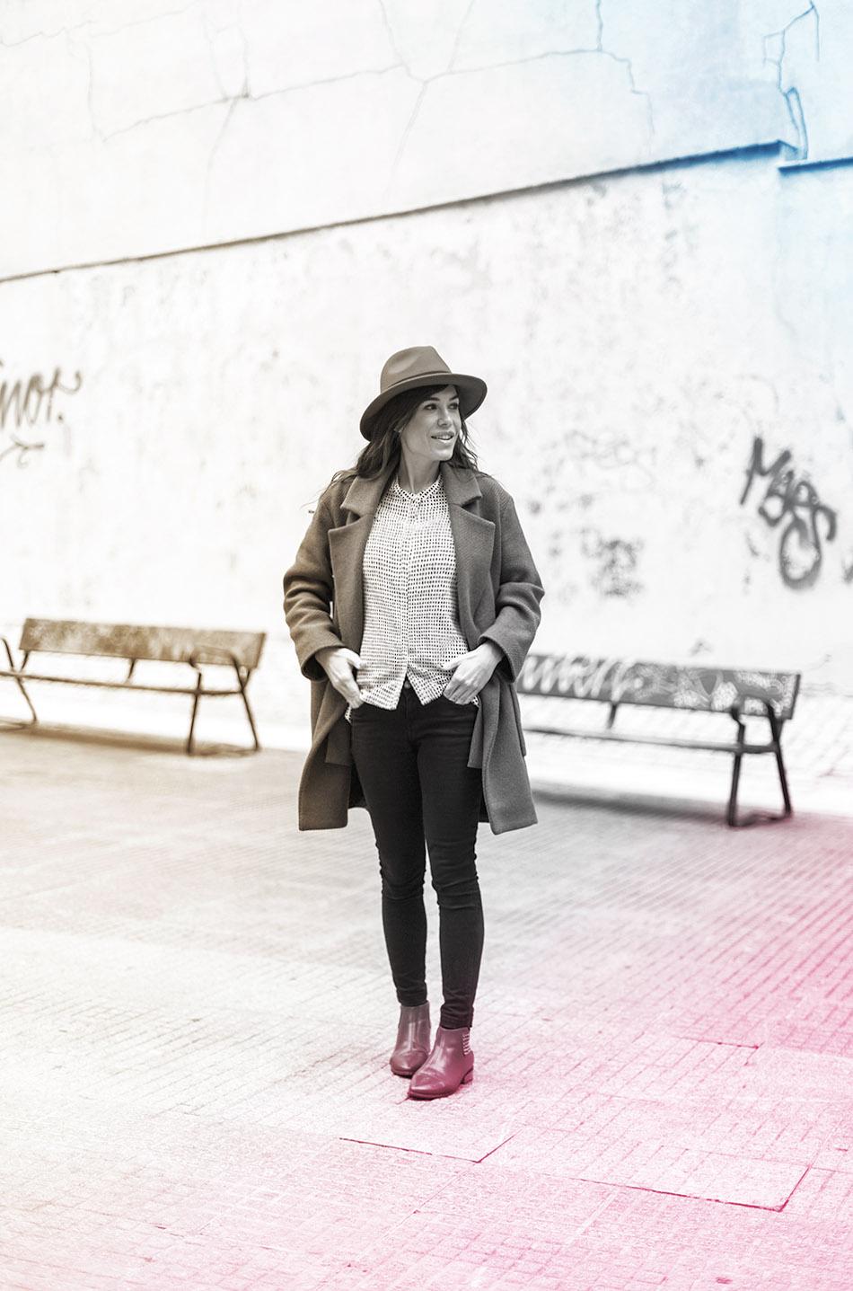 look de street style con abrigo marrón de lana, top de lunares  estilo naif, jeans pitillos, botines rojos y sombrero rojo
