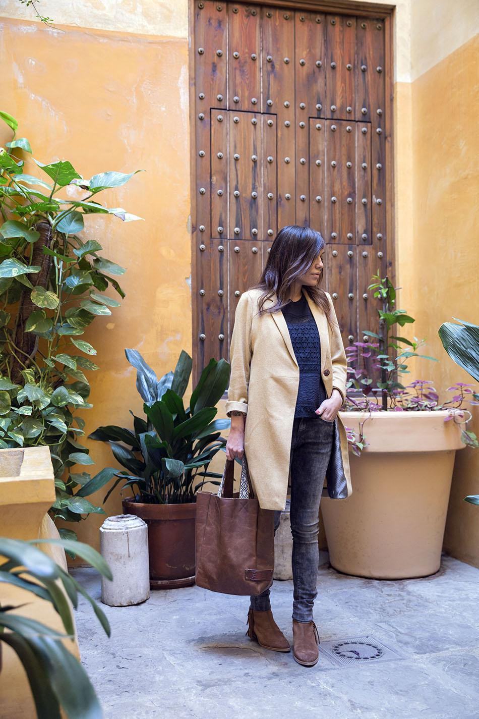 look de street style con abrigo tipo levita de Hakei, top de batista perforada y volante de Ralph Lauren, jeans desgastados y bolso estilo shopping
