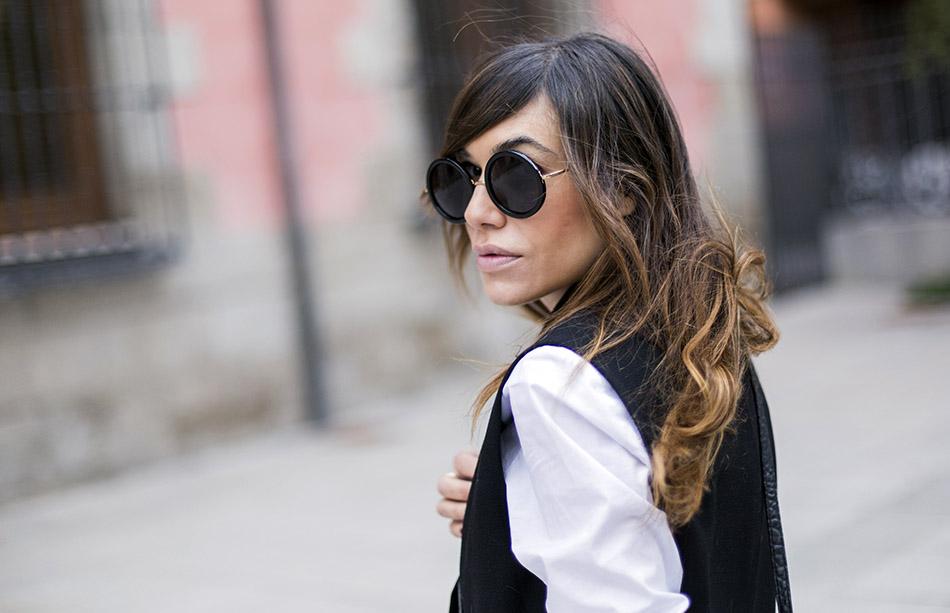 gafas Lennon. look de street style con camisa blanca masculina de hakei, leggins estilo moto de HM, botines con tachuelas doradas y bolso bandolera con print en blanco y negro