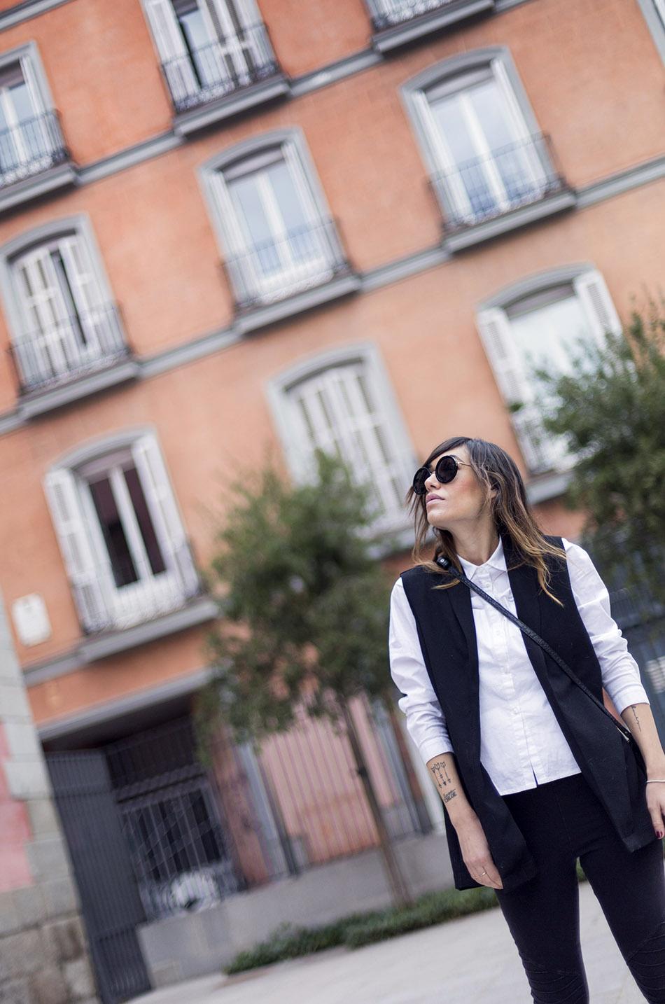 look de street style con camisa blanca masculina de hakei, leggins estilo moto de HM, botines con tachuelas doradas y bolso bandolera con print en blanco y negro