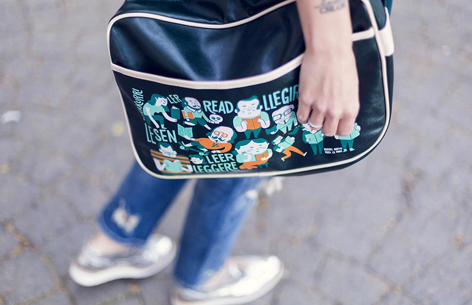 look de street style con blazer masculina en color verde esmeralda, top romántico de hake con volante en el bajo, denim ripped jeans, zapatos oxford plateados y bandolera ilustrada de FNAC