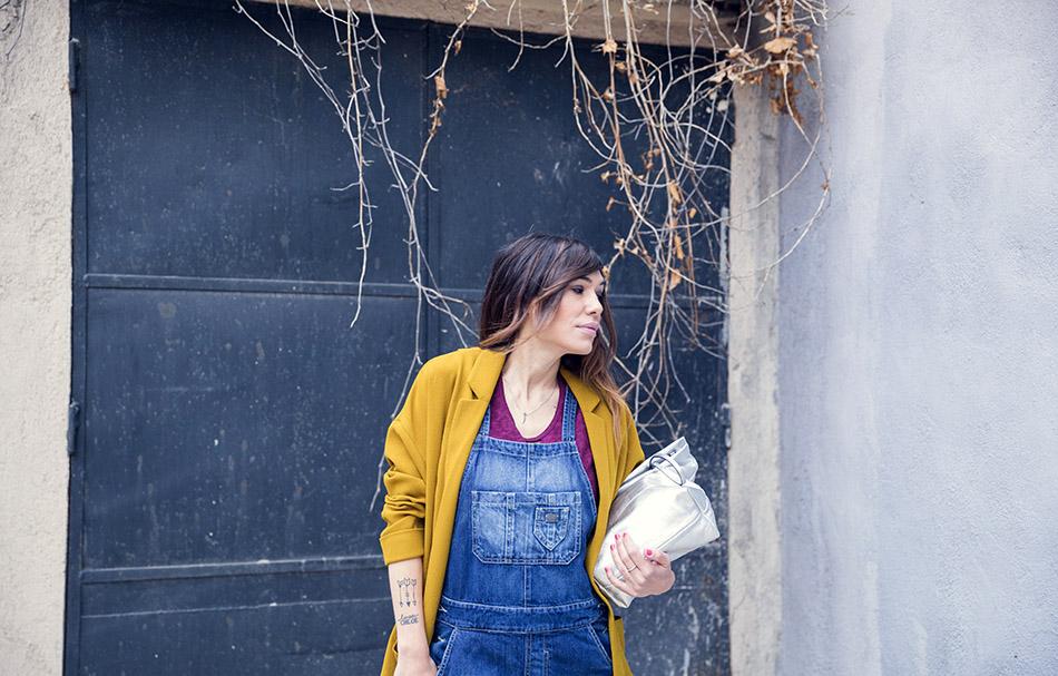 look de steetstyle con mono vaquero, camiseta de color granate, chaqueta de color mostaza, botines plateados y bolso tipo sobre plateado