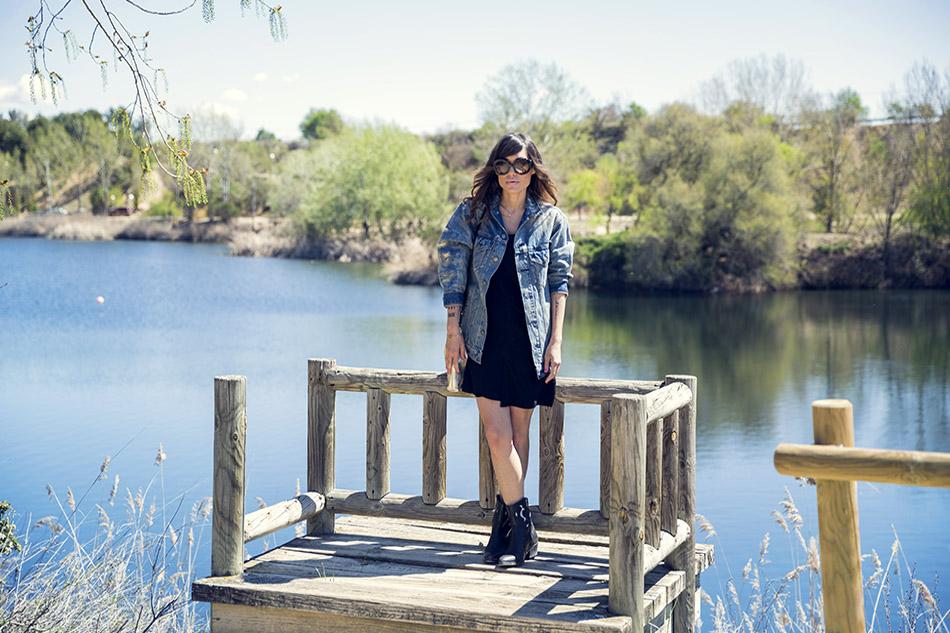 look de street style con vestido corto negro (little black dress), botines de Hakei, cazadora vaquera de oversize desgastada y pulsera de Tous