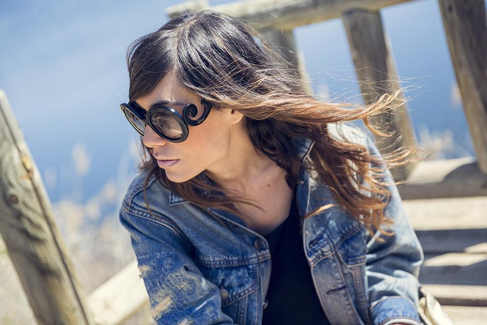 gafas de sol prada baroque look de street style con vestido corto negro (little black dress), botines de Hakei, cazadora vaquera de oversize desgastada y pulsera de Tous