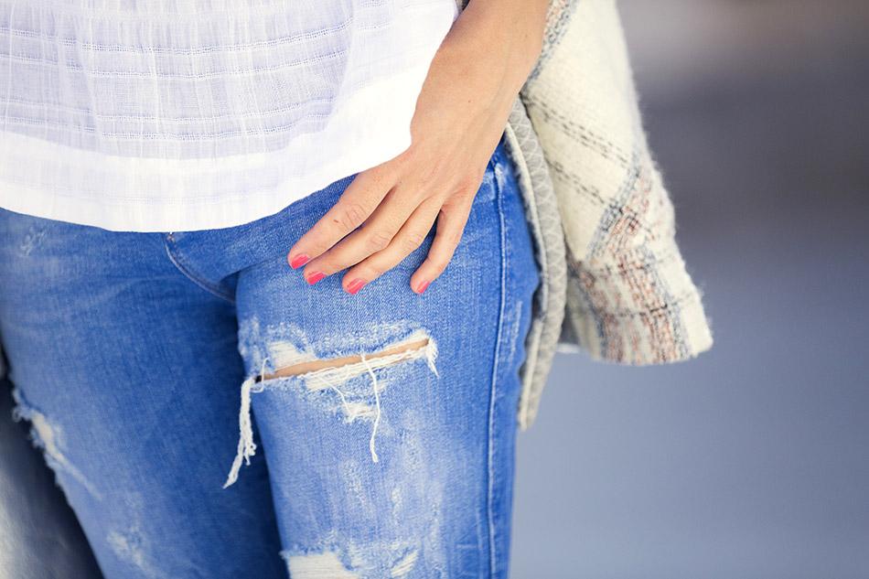 look de street style con chaqueta de anna studio blanca con detalles de estampado de cuadros, top de algodón blanco con ribete étnico, ripped jeans en azul cobalto, botines de ante con flecos, gafas de espejo azules claras y bolso bandolera plateado