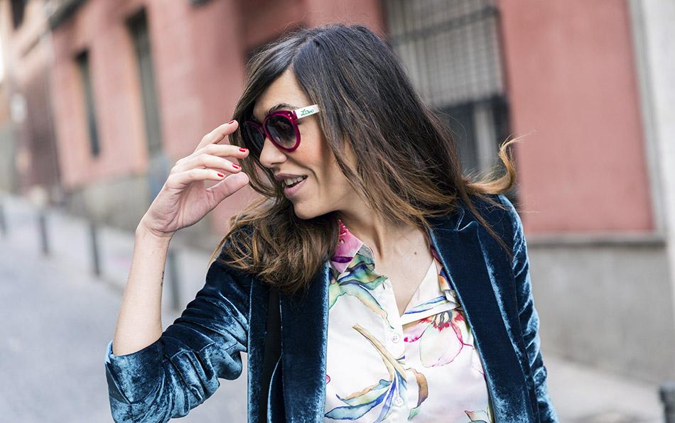 Look de street style con blazer de terciopelo en color verde, blusa de flores, ripped jeans, botines arson y bolso bandolera estilo saco