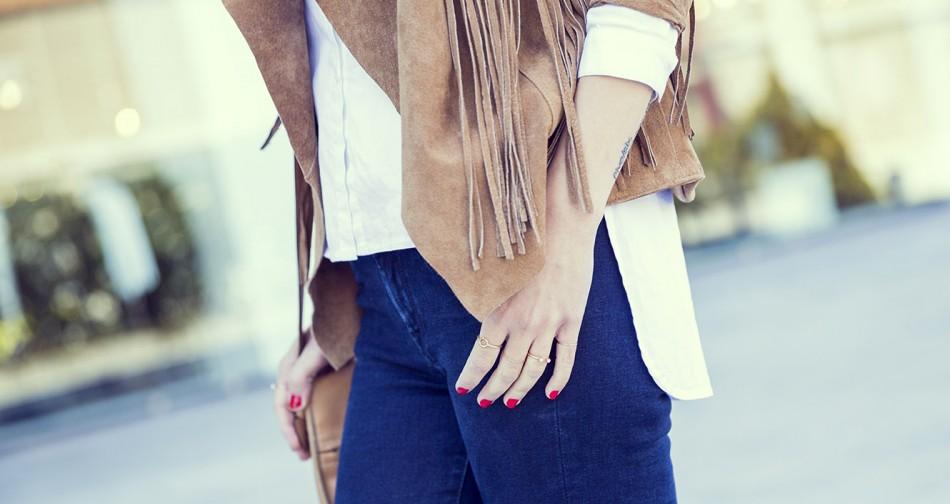 look de street style con chaqueta de ante con flecos, camisa blanca, jeans pitillo y sneakers