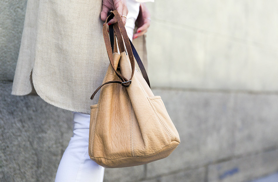 look de street style con levita de lino en color crudo, blusa con volante en el bajo, ripped jeans en color blanco, botines de ante en marrón claro y bolso tipo saco