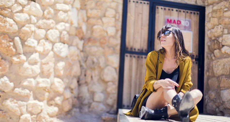 Look de street style con abrigo ligero estilo levita de hakei en color mostaza y LBD de American Vintage con botines estilo cowboy de hakei y bolso Chanel