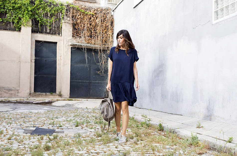 look de street style con vestido sedoso azul marino de american vintage, zapatos plateados estilo oxford , bolso gris de purificación garcia