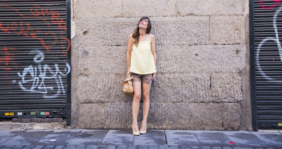 look de street style con top amarillo de tirantes combinado con shorts de ante en color marrón, zapatos de tacón en charol de mango y bolso de miu miu