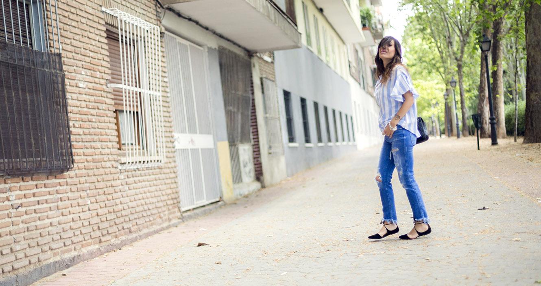 look de street style con top de rayas verticales azules y blancas y coolants en las mangas, jeans pitillos desgastados, sandalias planas tipo bailarina y bolso de Chanel