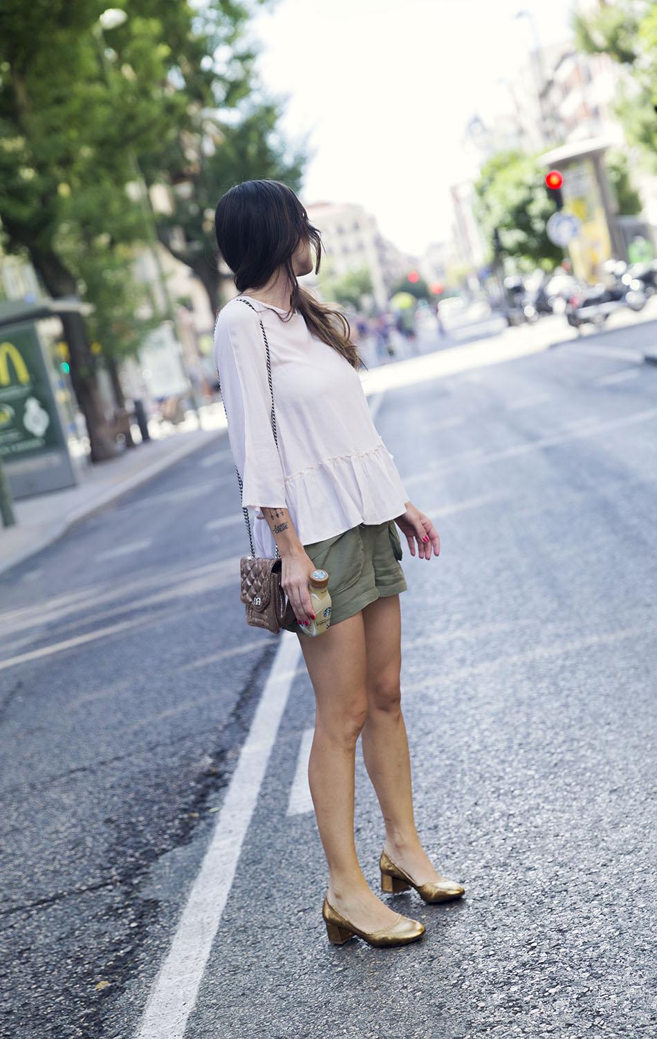look de street style con camisa en color nude , manga al codo y volante en el bajo, shorts estilo safari en color verde militar, zapatos en color dorado oscuro y mini bolsito estilo chanel pequeño en color dorado. bebida starbucks