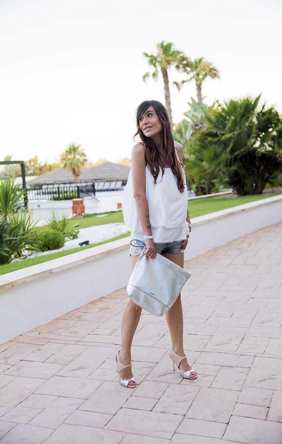 look de street style con top de tirantes blanco, shorts vaqueros con detalle de ganchillo, sandalias de tacón plateadas de zara y bolso tipo cartera plateado