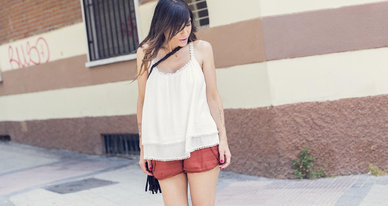 look de street style con top de tirantes en color blanco y pantalón corto en color caramelo, con sandalias planas de cuero y bolso pequeño de ante estilo bandolera con flecos