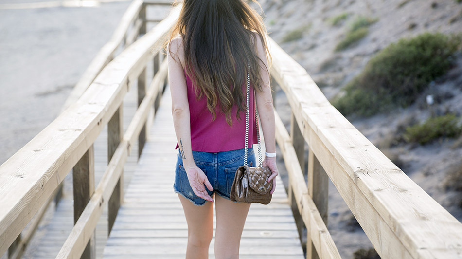look de street style con top de tirantes estilo crop top de Mango en color coral, shorts denim, sandalias y bolso dorado con cadena