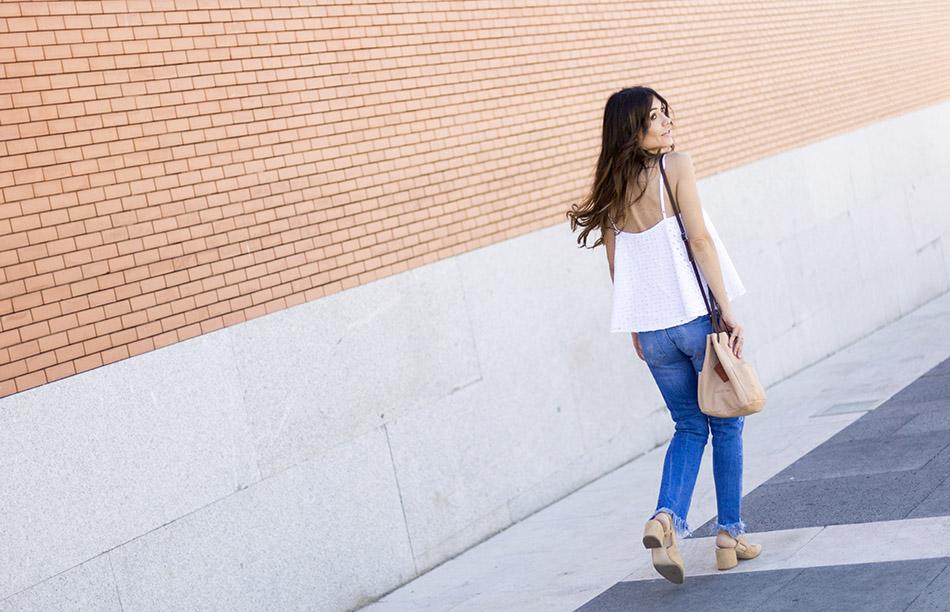 look de street style con top de tirantes blanco de batista perforada, pantalones vaqueros pitillos desgastados de Zara, sandalias de ante, tacón cuadrado y destalonadas de zara y bolsito estilo saco