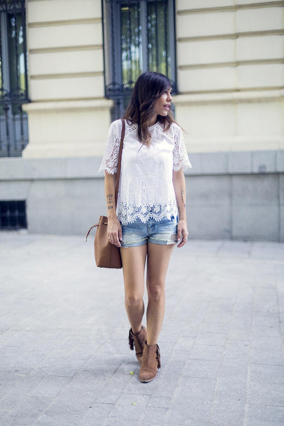 look de street style con shorts desgastados en tejido denim, blusa blanch con detalle de calados o crochet y abertura en la espalda y botines