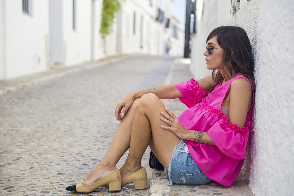 look de street style con top de color fucsia y estilo cut off the shoulders, shorts denim, zapatos bicolor estilo chanel de zara y bolso acolchado de hakei