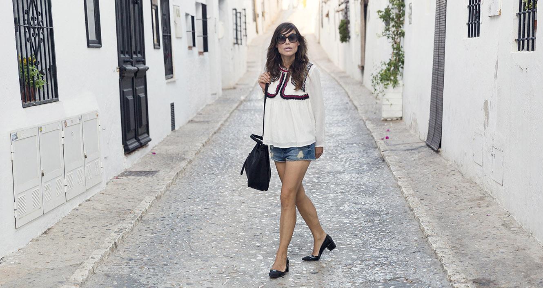 look de street style con blusa de color blanco y detalle de bordados en la zona del pecho, shorts denim, zapatos de tacón midi ancho y bolso estilo saco de zara