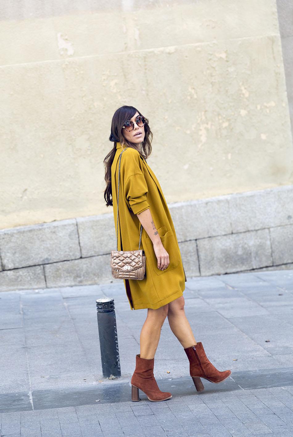 look de street stye con levita de color mostaza y vestido de ante marrón de hakei, y botines de ante color caramelo y bolsito acolchado dorado de Hakei
