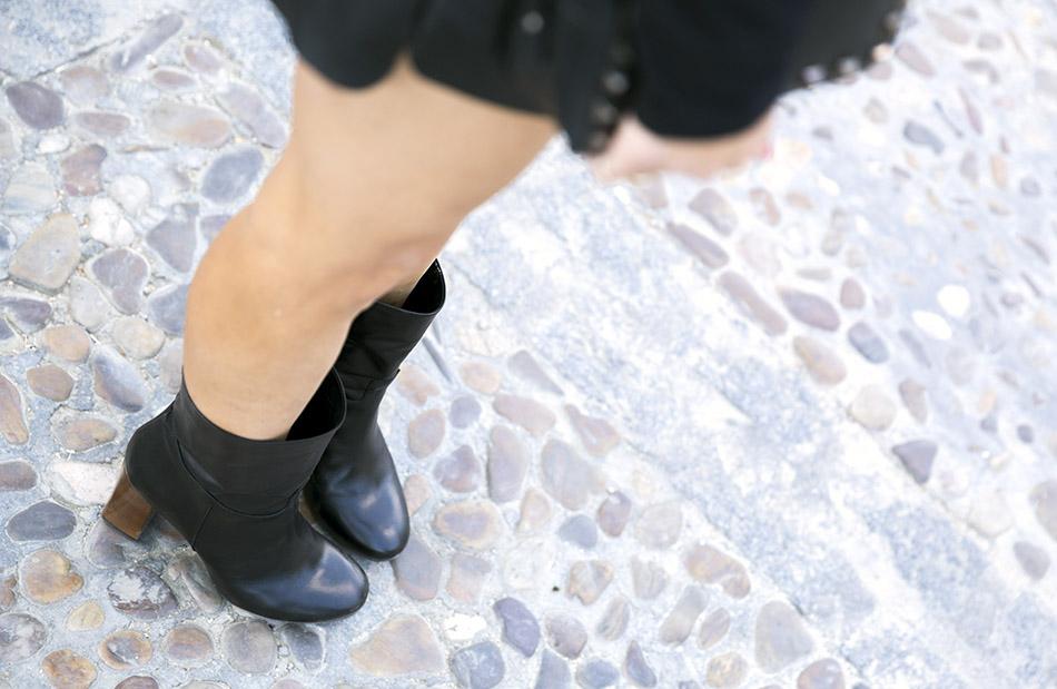 look de street style con top de estilo victoriano con ribetes en puños de color negro, shorts de polipiel negros, botines negros con tacón de madera y bolso al hombro con tachuelas plateadas