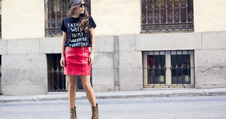 look de street style con camiseta negra con mensaje y falda biker de cuero brillante rojo de Mango, botines de animal print leopardo