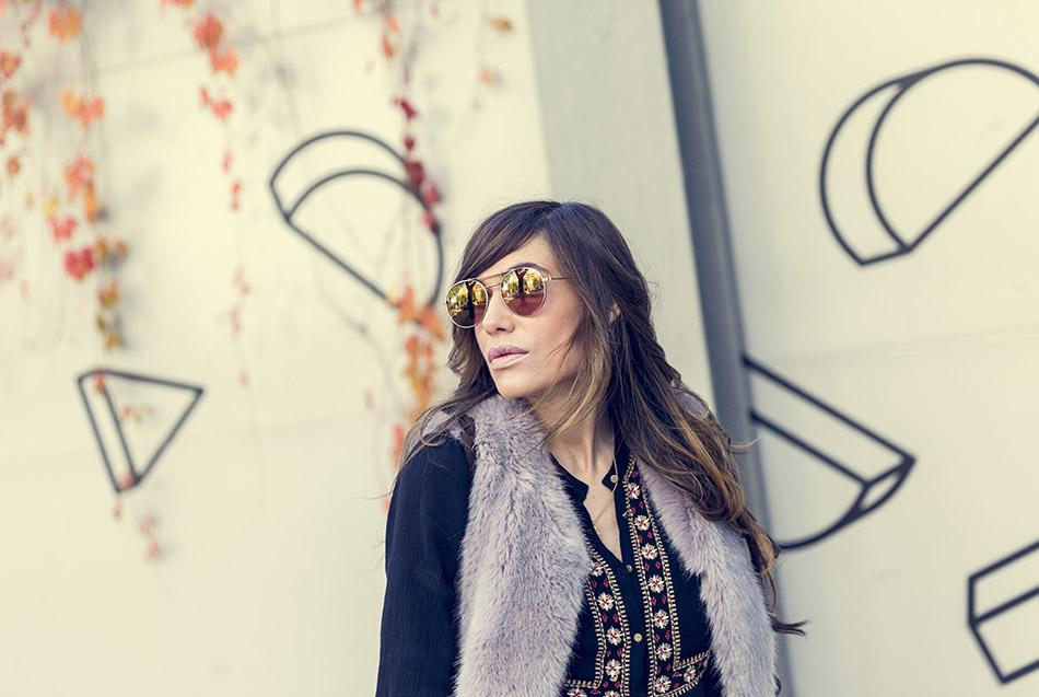 look de street style con chaleco de pelo de color malva, blusa con bordados de estilo boho de Kiabi, pantalones pitillos brillantes negros de H&M, botines y bolso de ante con flecos