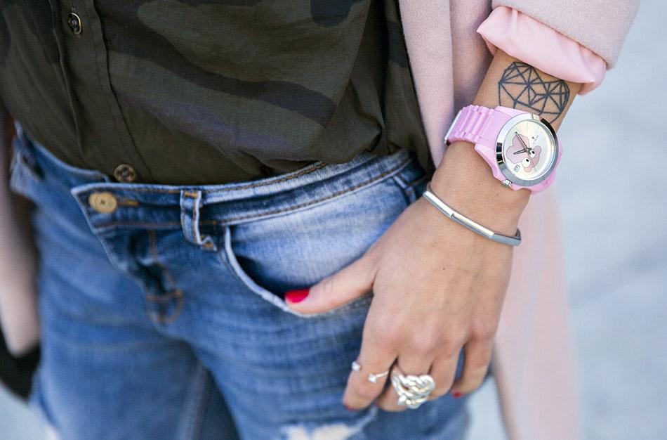 look con abrigo rosa, camisa con estampado de camuflaje y tachuelas, jeans rotos y desgastados de Mango, botines negros y reloj de Tous