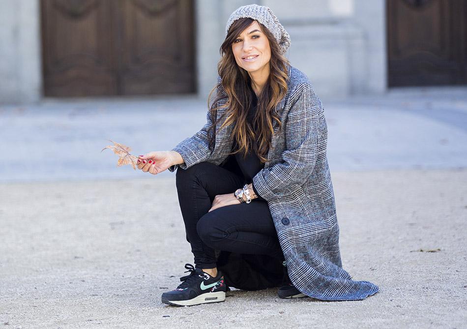 look de street style con abrigo de corte masculino, recto y ligeramente oversize, jeans pitillos y sudadera negra, zapatillas de deporte de Nike air max