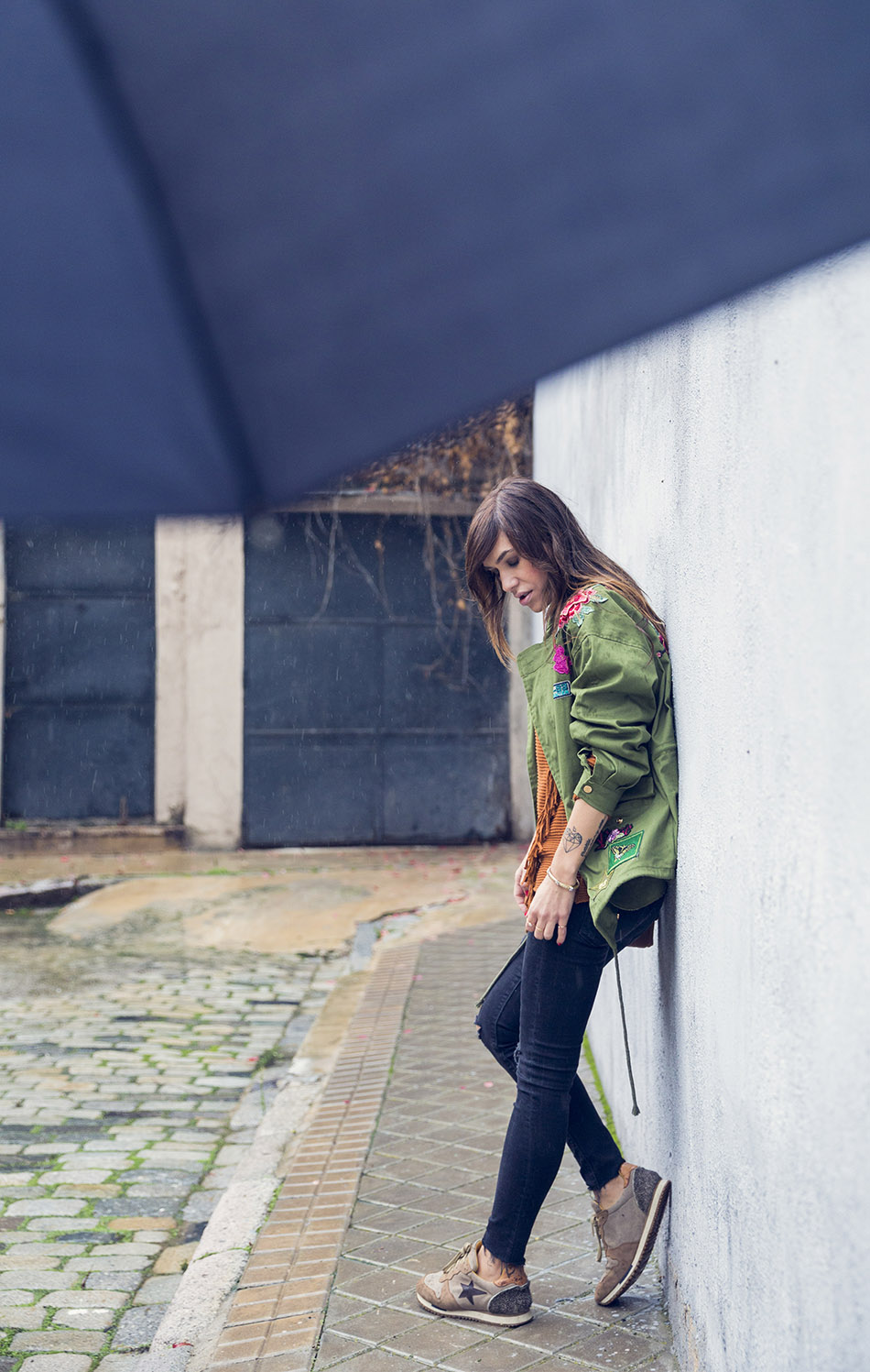 look de street style con parka con flores bordadas, jersey en color caramelo con flecos, jeans pitillo con rotos y desgastados, deportivas y bolsito al hombro de piel marrón