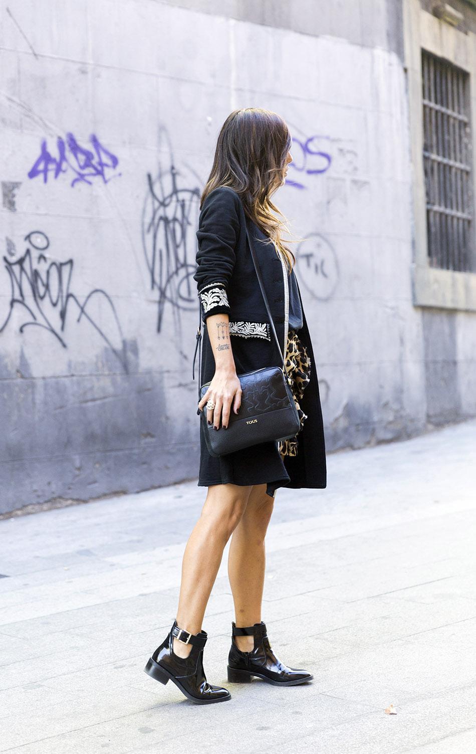 look de street style con levita de estilo militar u officer band, camiseta básica negra, falda mini de estampado animal, botines negros con hebilla y bolso al hombro de Tous
