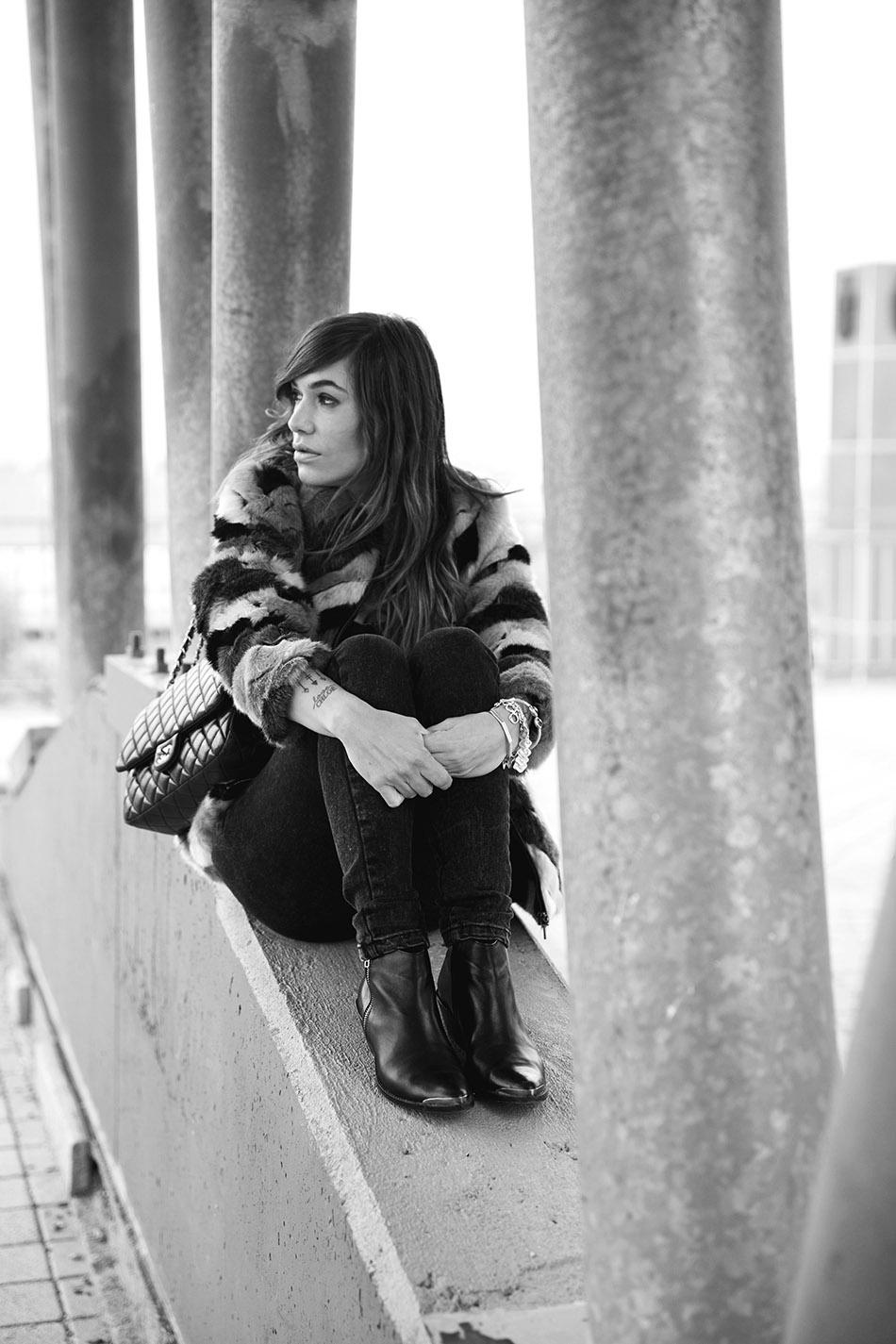 look de street style con chaqueta de pelo de conejo en tonos grises, mono vaquero de color negro, botines de cuero y bolso de chanel