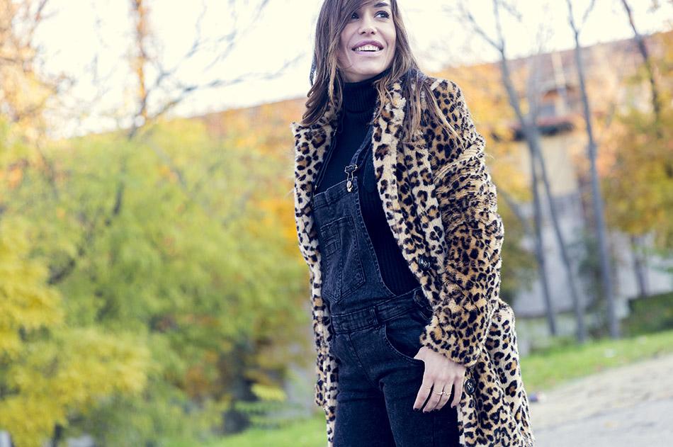look de street style con abrigo de animal print, peto vaquero en color negro, sneakers grises y jersey de cuello alto negro
