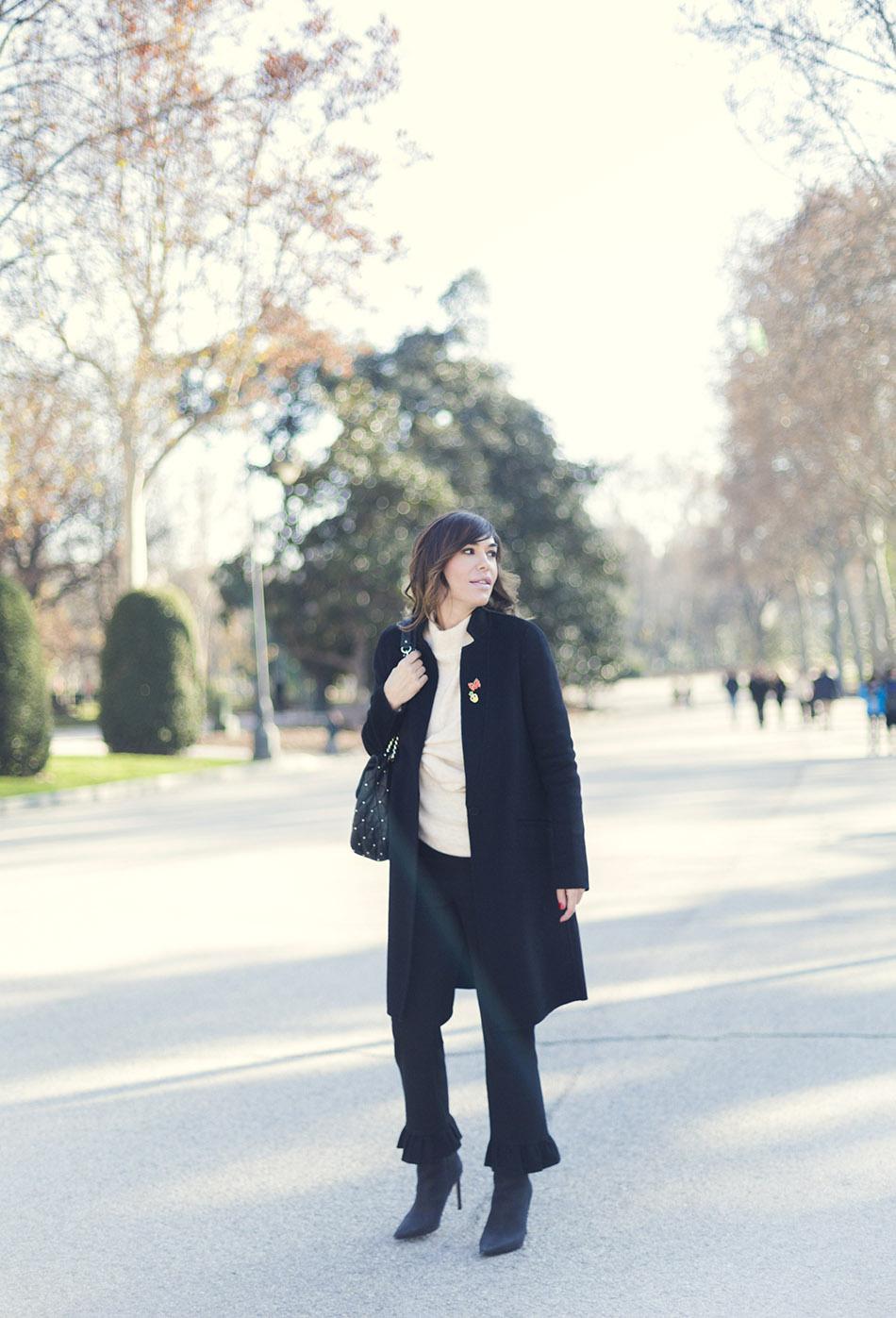 look de street style con abrigo recto negro de Zara, jersey de lana en color crudo con detalle de nudo en el delantero de Mango, pantalón de vestir con volante en el bajo de Zara y botines negros de tacón