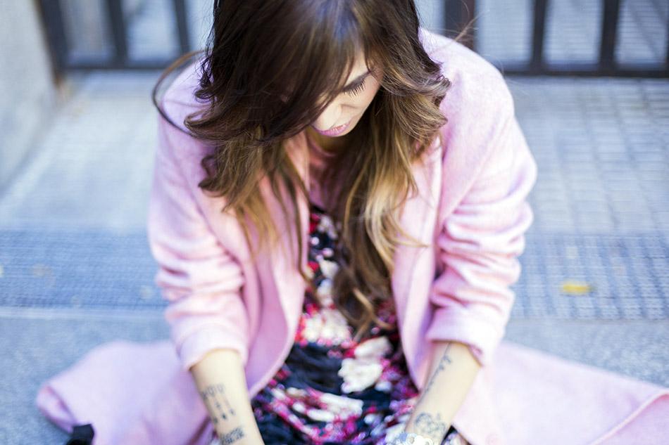 look de street style con abrigo largo de lana de color rosa de Zara, vestido de tirantes de flores con camiseta por debajo y botines de Zara