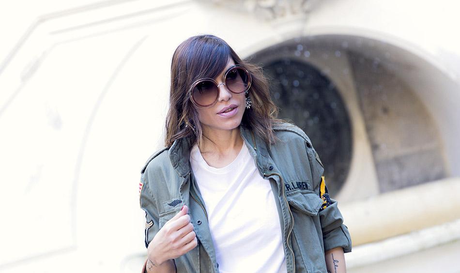 look de street style con trench militar de Ralph Lauren, camiseta básica blanca, falda midi plisada metalizada, sneakers blancas y gafas de Chloé