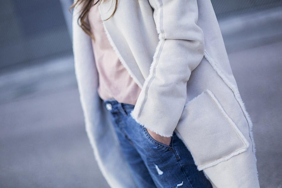 look de street style con abrigo reversible de ante, camiseta con mensaje de mango, jeans boyfriend de reiko, botines de antes y flecos, y bolso de cuero marrón de hakei