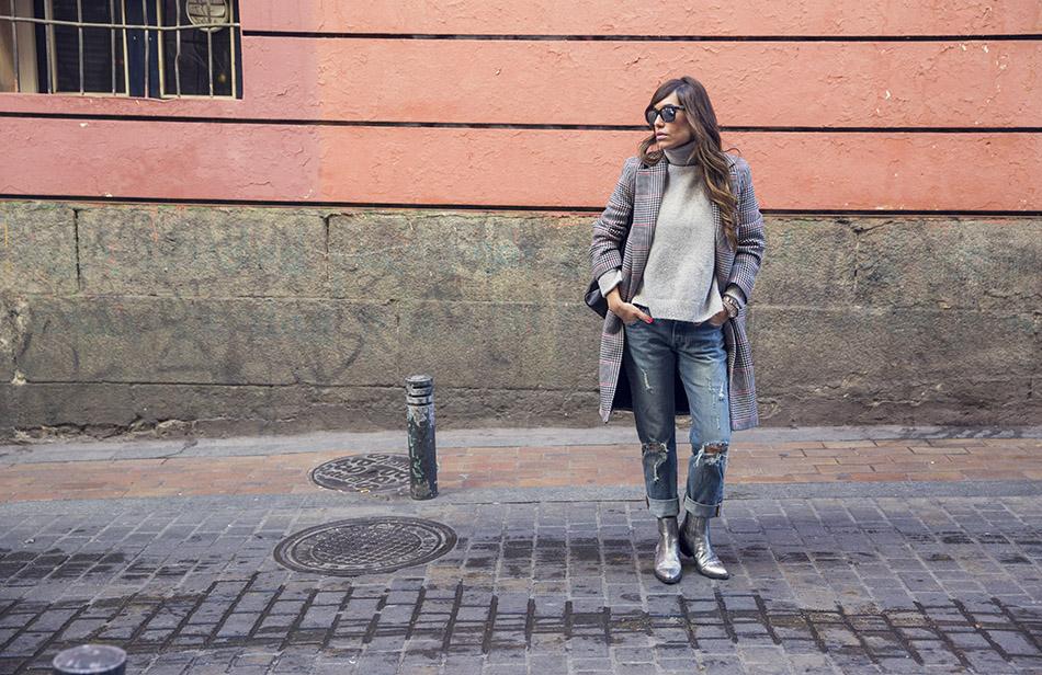 look de street style con jersey de cuello alto de cashmere en color gris, abrigo masculino con print príncipe de gales, jeans y botines plateados