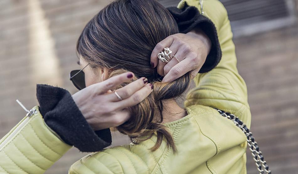 look de street style con cazadora de cuero amarilla , jersey negro con mangas acampanadas, jeans rotos negros, deportivas negras de no name y rayban negras