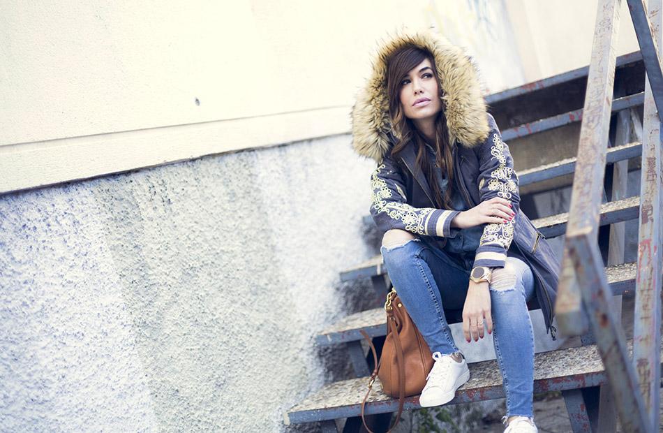 look de street style con parka de estilo militar, camisa vaquera, jeans Reiko y sneakers blancas de Mango
