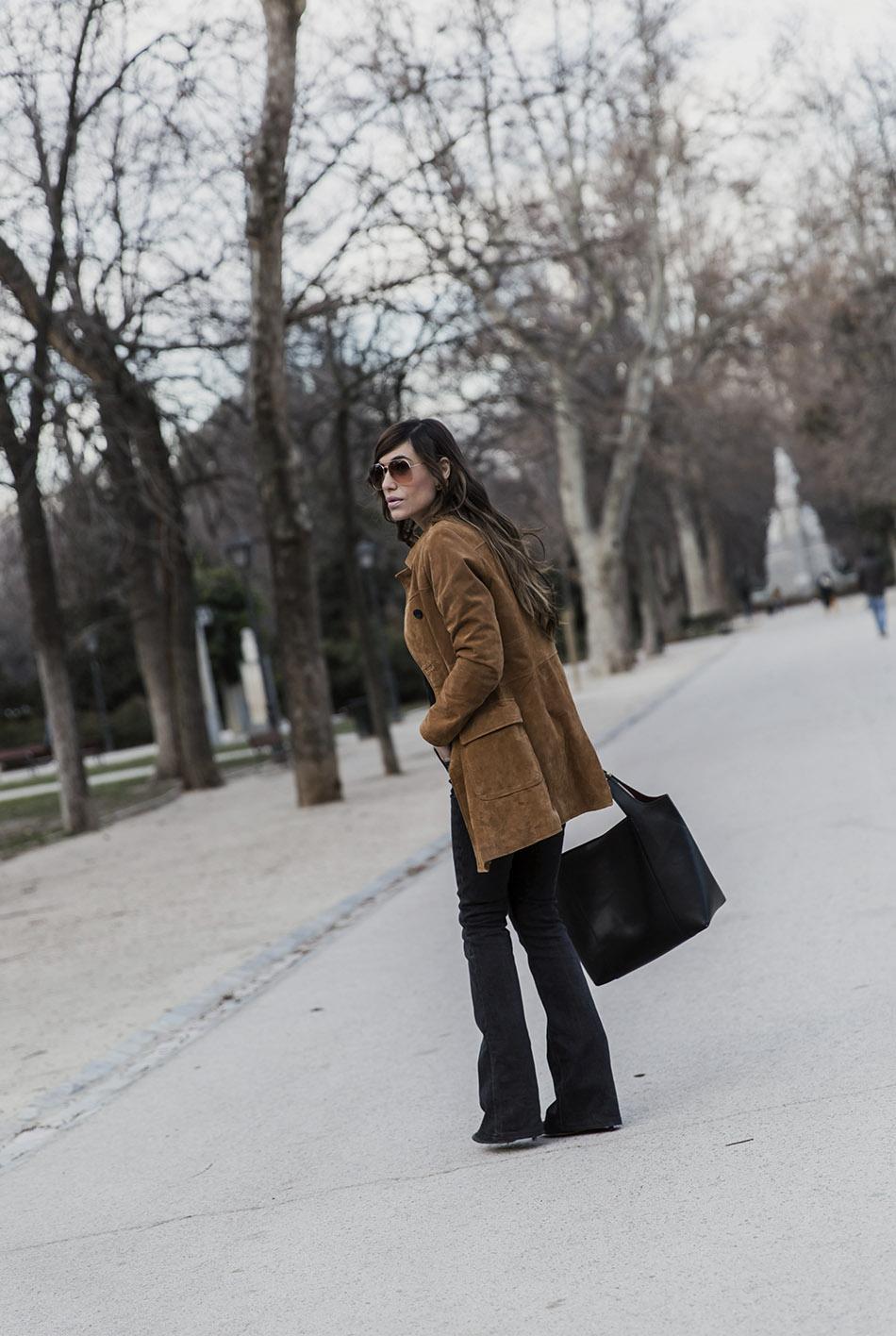 look de street style con abrigo tipo levita de ante en color camel, jersey negro con detalle de flores bordadas y flared jeans
