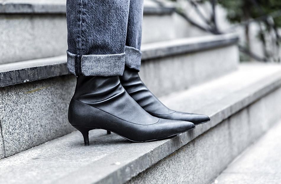 look de street style con chaquetón de pelo de color blanco, jersey negro, relaxed jeans, botines con kitten heels y bolso de chanel