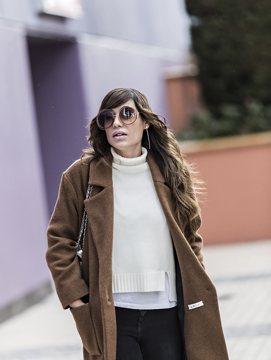look de street style con abrigo marrón de lana, jersey de cuello alto blanco de shein, jeans pitillo negros, deportivas blancas con detalle dorado, gafas Michael Kors, y gafas Chloé