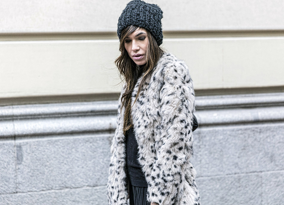 look de street style con gorro de lana negro, jersey de cuello alto negro, pantalones tableados culottes, deportivas nike, abrigo de pelo animal print y bolso chanel