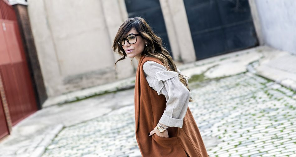 look de street style con chaleco de lana largo, blusa con volante de color beige, mom jeans rotos, bolso al hombro de Michael Kors, reloj Tous